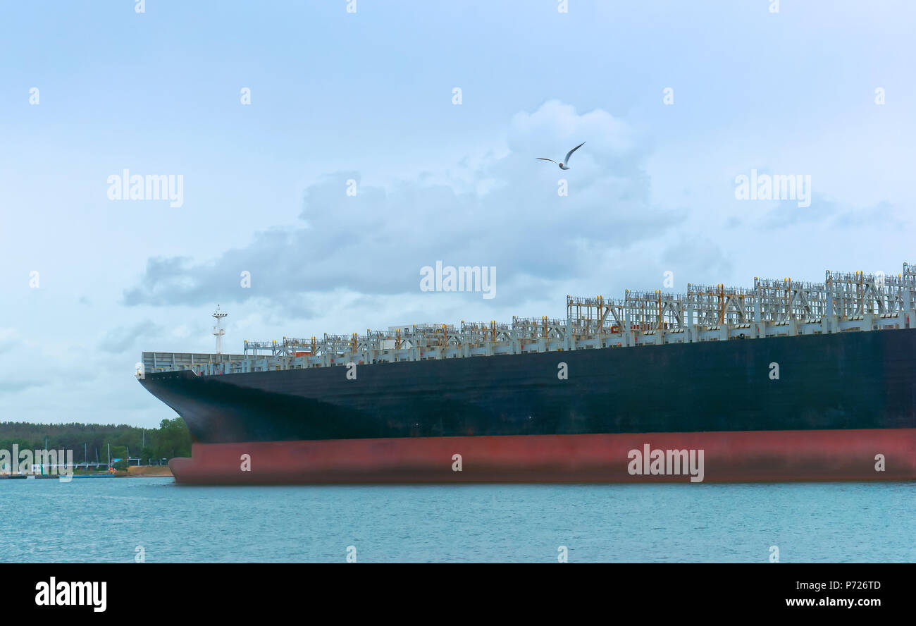 huge empty container ship, blue cargo ship on water - Stock Image