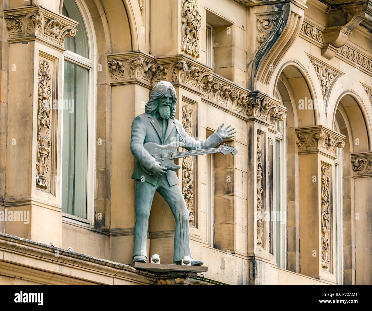 Statue of George Harrison playing a guitar outside Hard Day's Night Hotel, North John Street, Liverpool, England, UK - Stock Image