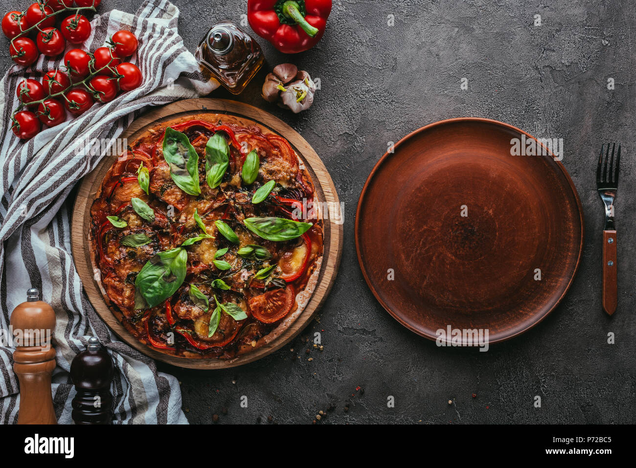 top view of delicious pizza with rustic plate on concrete table - Stock Image