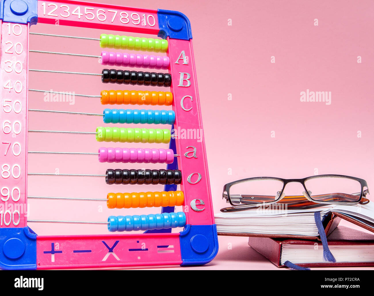 Colored Abacus, Glasses and Notebook on pink background. Education, back to school concept - Stock Image
