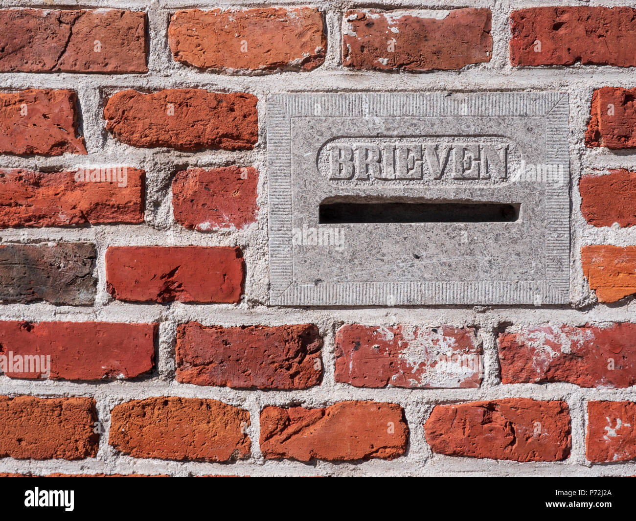 Old stone letterbox in brick wall, with the Dutch text 'letters'. Photographed in the city of Groningen. - Stock Image