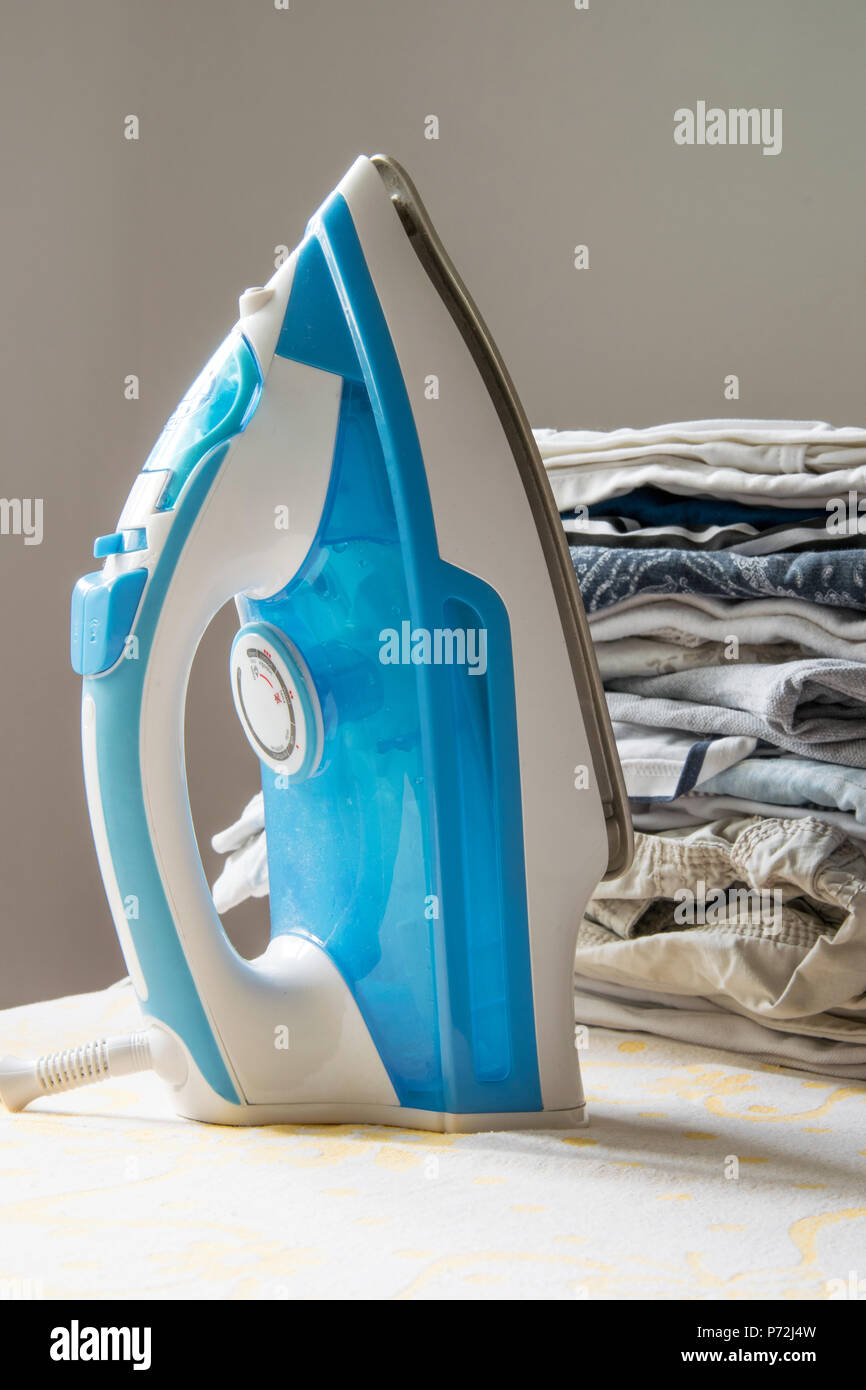 Indoor housework - steam iron and pile of folded clothes - Stock Image