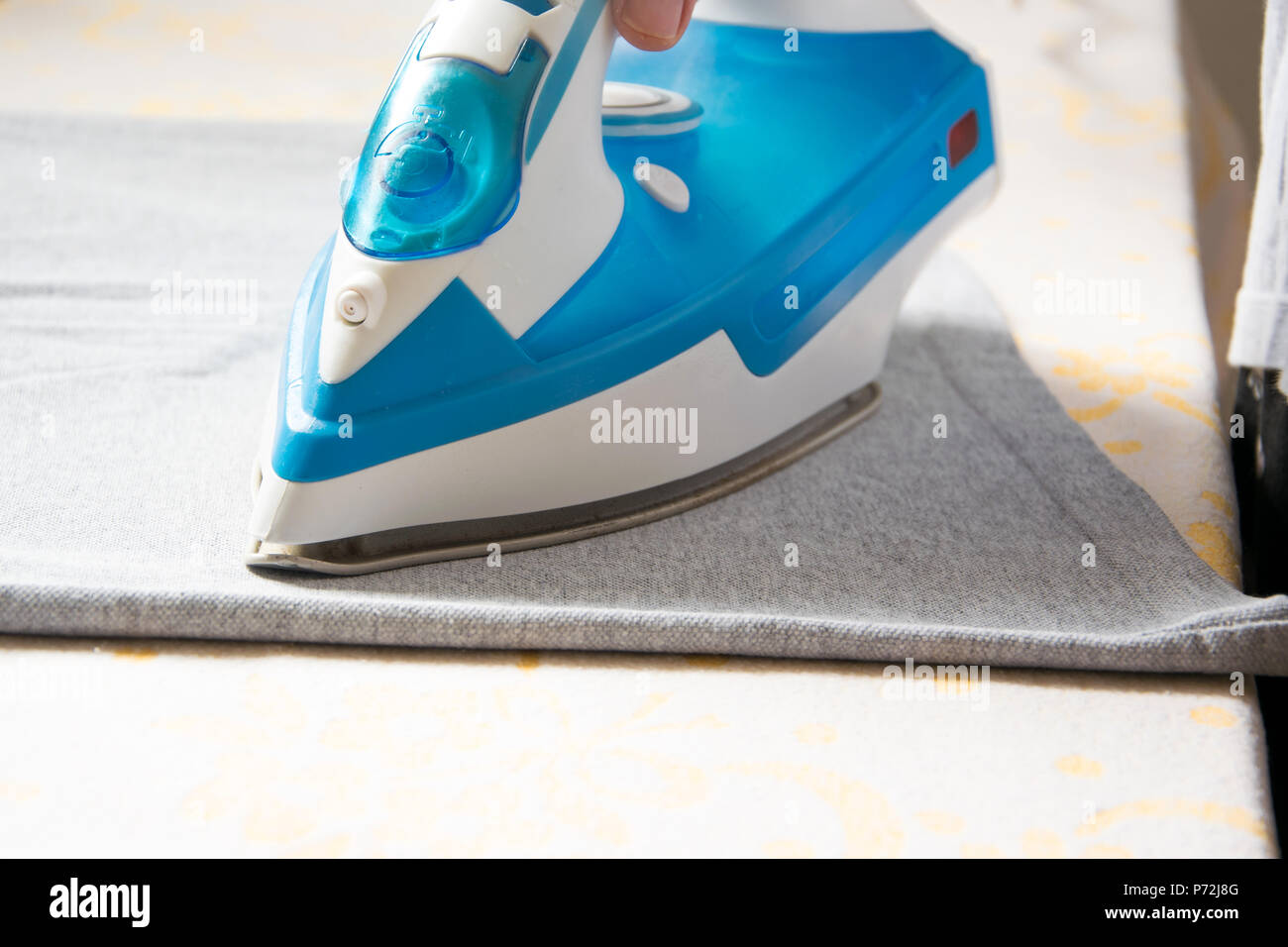 Close up view of female hand ironing a t-shirt with steam iron, housework concept - Stock Image