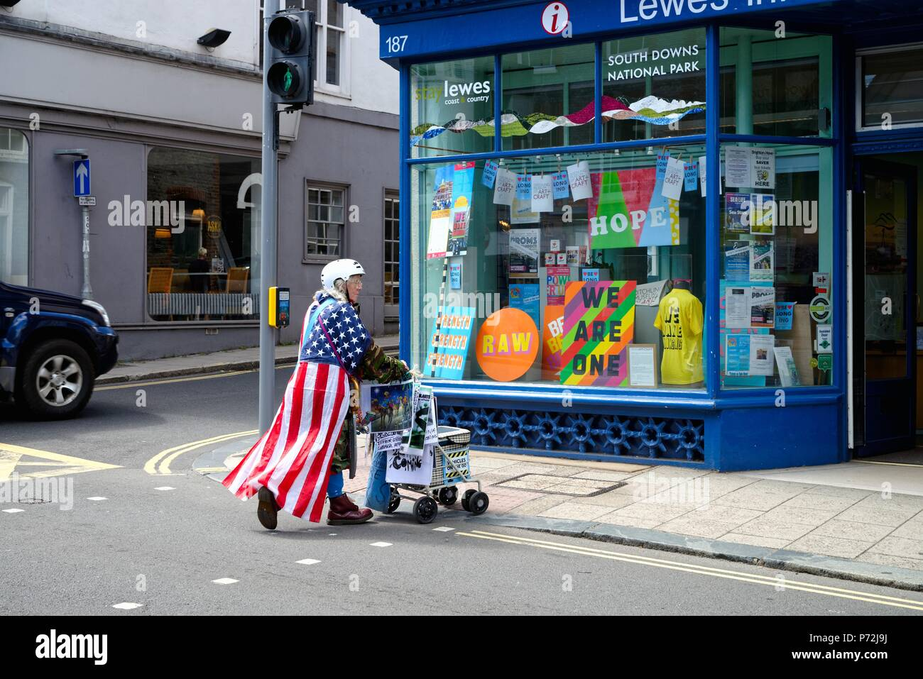 An elderly woman wearing a crash helmet and the american stars and stripes flag pushing a trolley with protest posters in Lewes high street Sussex UK - Stock Image
