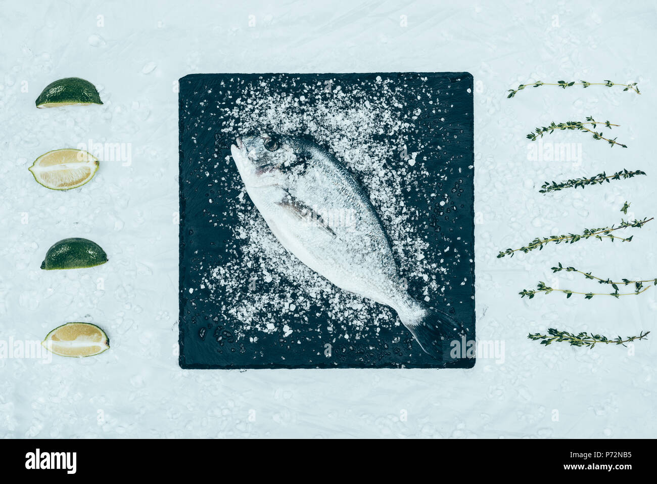top view of fresh raw dorado fish with on slate board and herbs with lime slices on grey - Stock Image