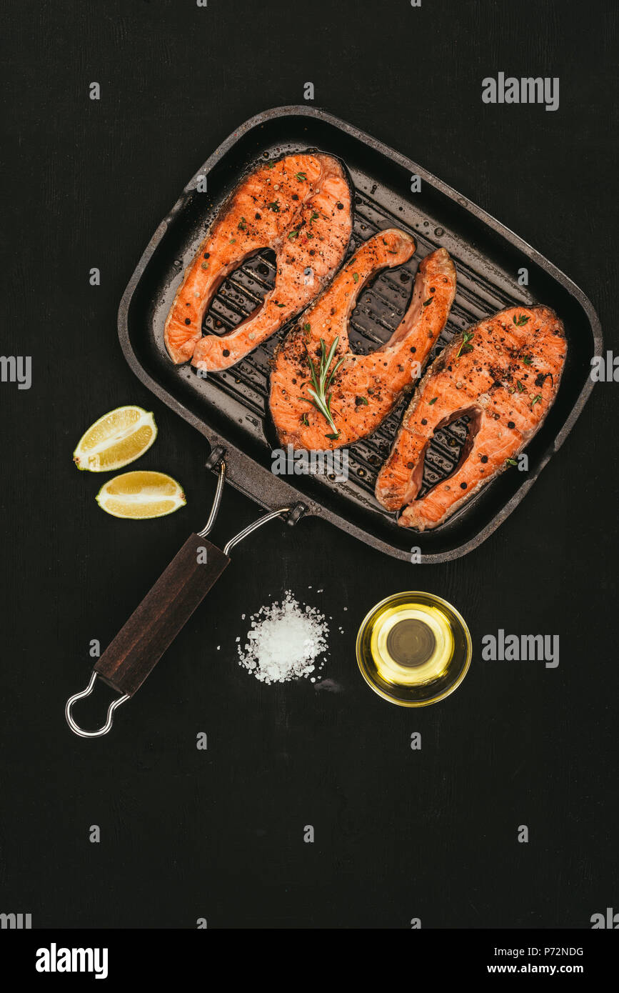 top view of salmon steaks on grill, salt, olive oil and lime slices on black - Stock Image