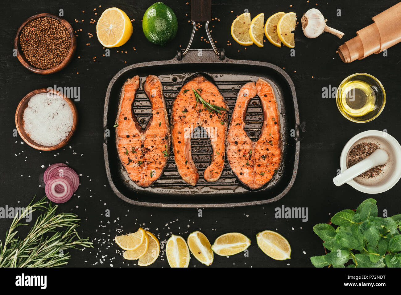 top view of salmon steaks on grill and spices on black - Stock Image