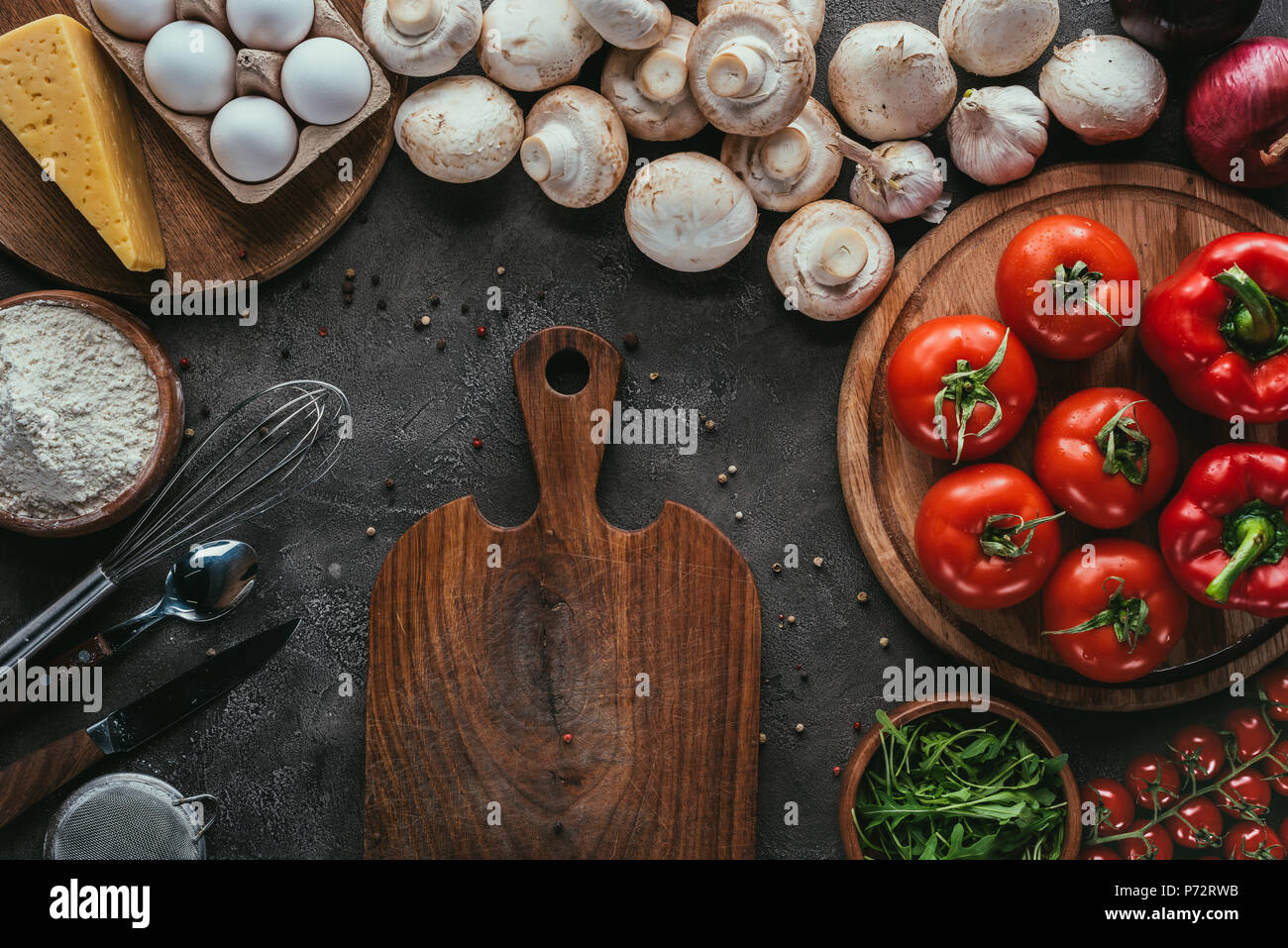 top view of different raw ingredients for pizza and cutting board on concrete surface - Stock Image