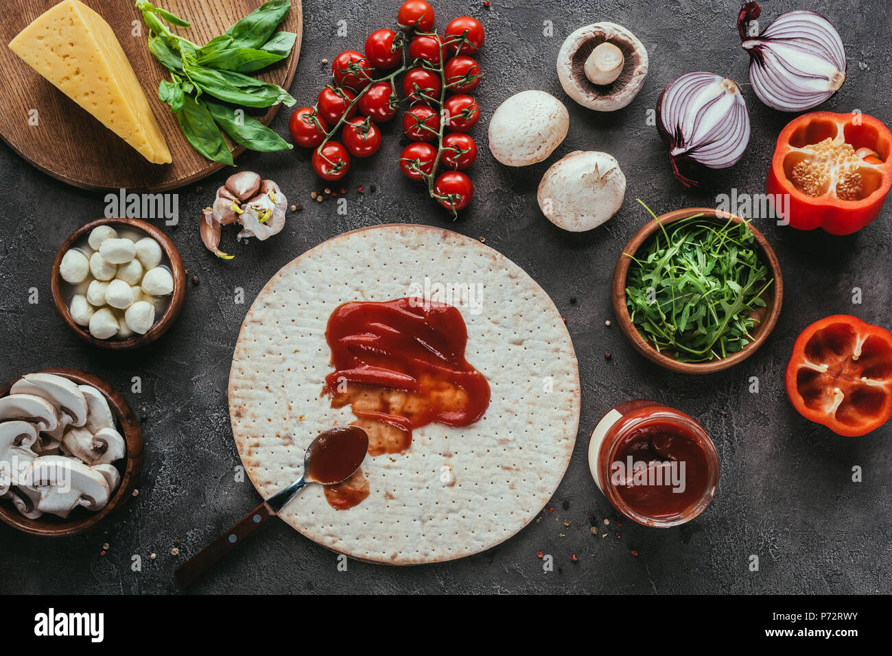 top view of pizza dough with poured ketchup and various vegetables on concrete table - Stock Image