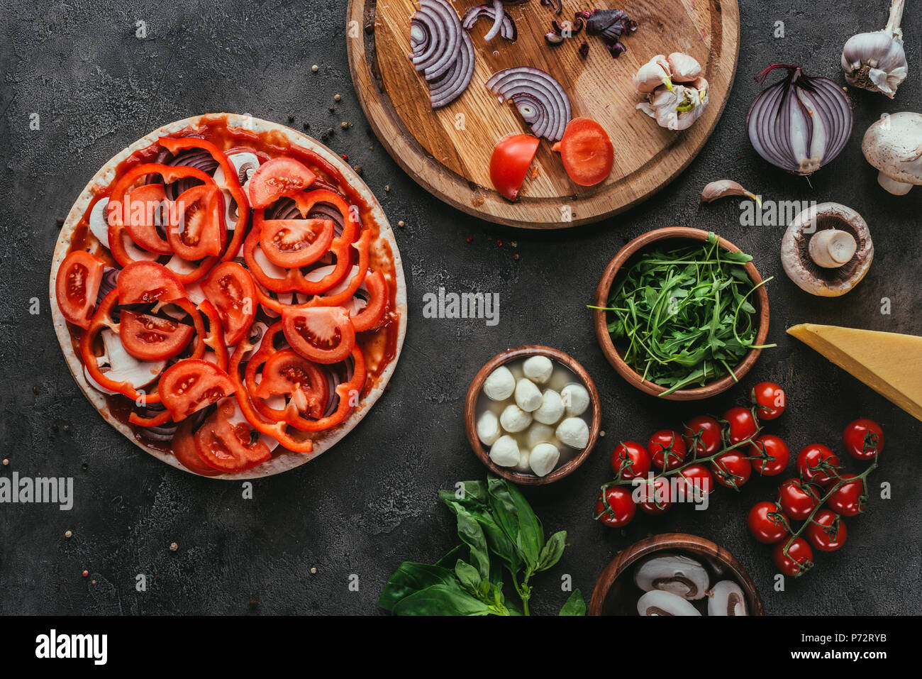 top view of uncooked pizza with different ingredients on concrete table - Stock Image