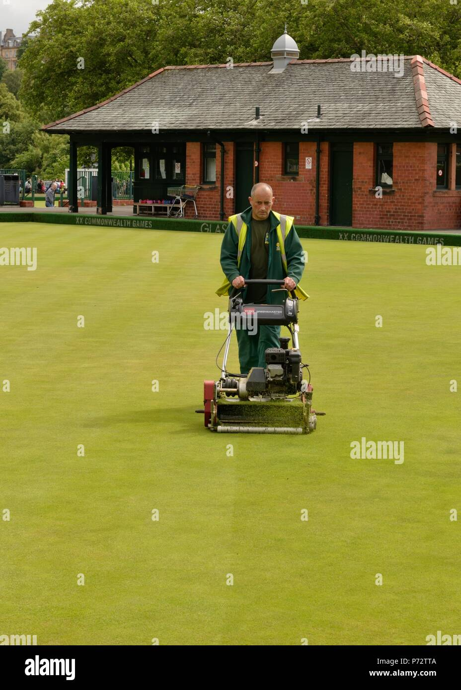 A Glasgow city council worker mowing the bowling green lawn at Kelvingrove, Glasgow, Scotland, UK - Stock Image