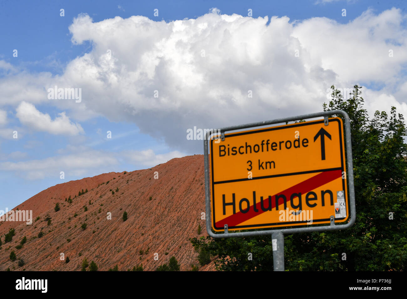 Bischofferode, Deutschland. 27th June, 2018. 27.06.2018, Bischofferode, Thuringen: The town of Bischofferode is signposted on a sign in front of a spoil heap of the former Bischofferode potash plant. Protests of the miners at the close of the early 1990s made the work known nationwide. (to dpa 'hunger strike! - Search for clues 25 years after the Kali rebellion' from 28.06.2018) Credit: Jens Kalaene/dpa central image/dpa | usage worldwide/dpa/Alamy Live News - Stock Image