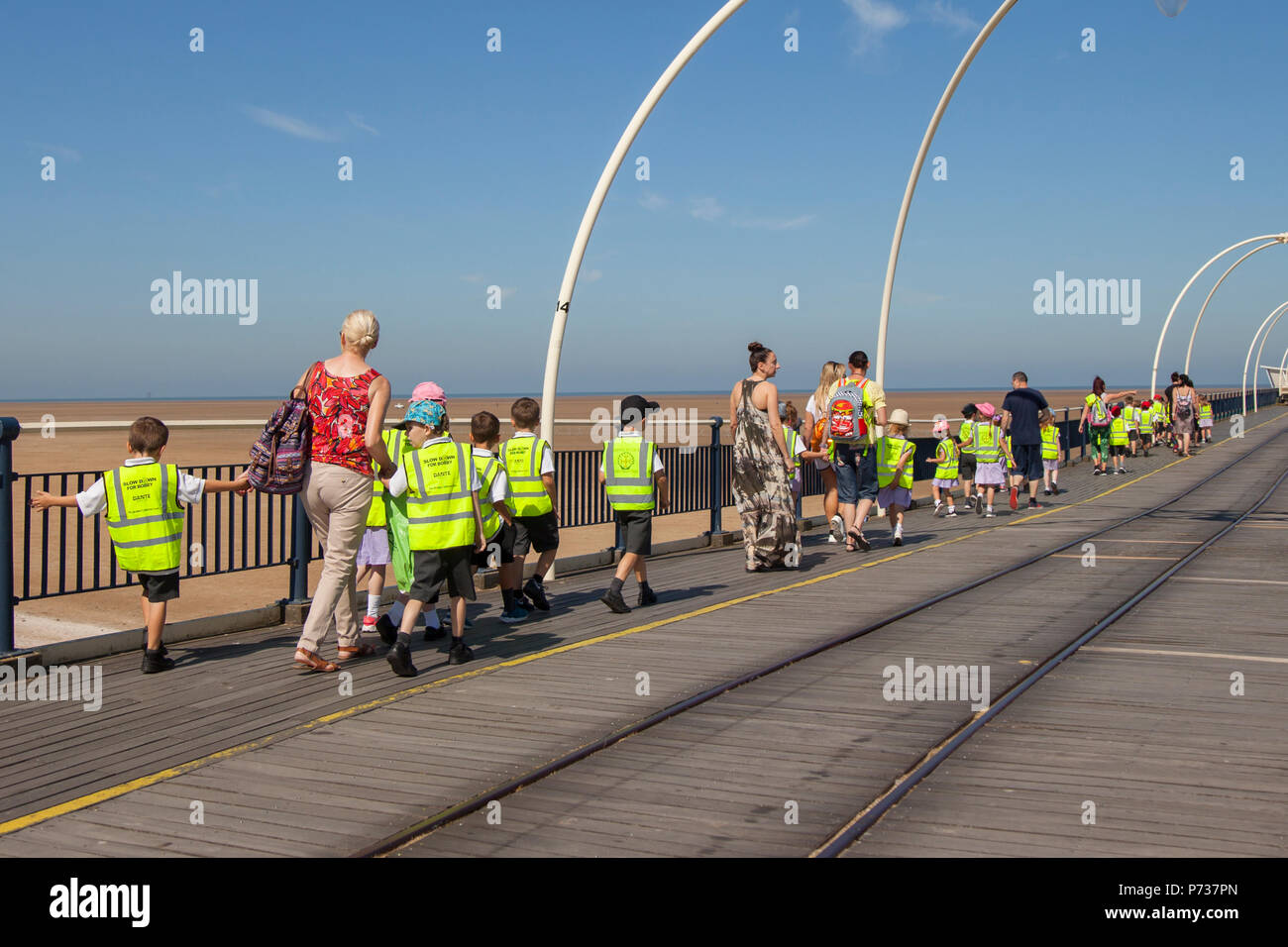 Southport, Merseyside, 4th July, 2018. UK Weather.  Blue skies & bright sun in the north-west as tourists, school children and visitors take a stroll on the seaside pier.  Credit:MediaWorldImages/AlamyLiveNews - Stock Image