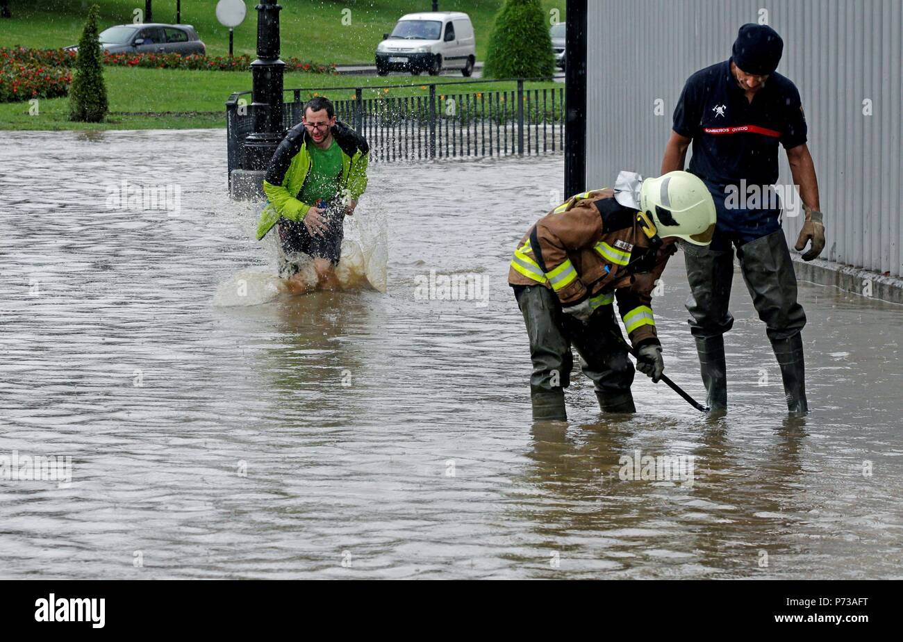 Oviedo, Spain. 04th July, 2018. Firefighters try to drain water in a flooded street in Oviedo, Spain, due to the heavy rains 04 July 2018. Credit: Alberto Morante/EFE/Alamy Live News Stock Photo