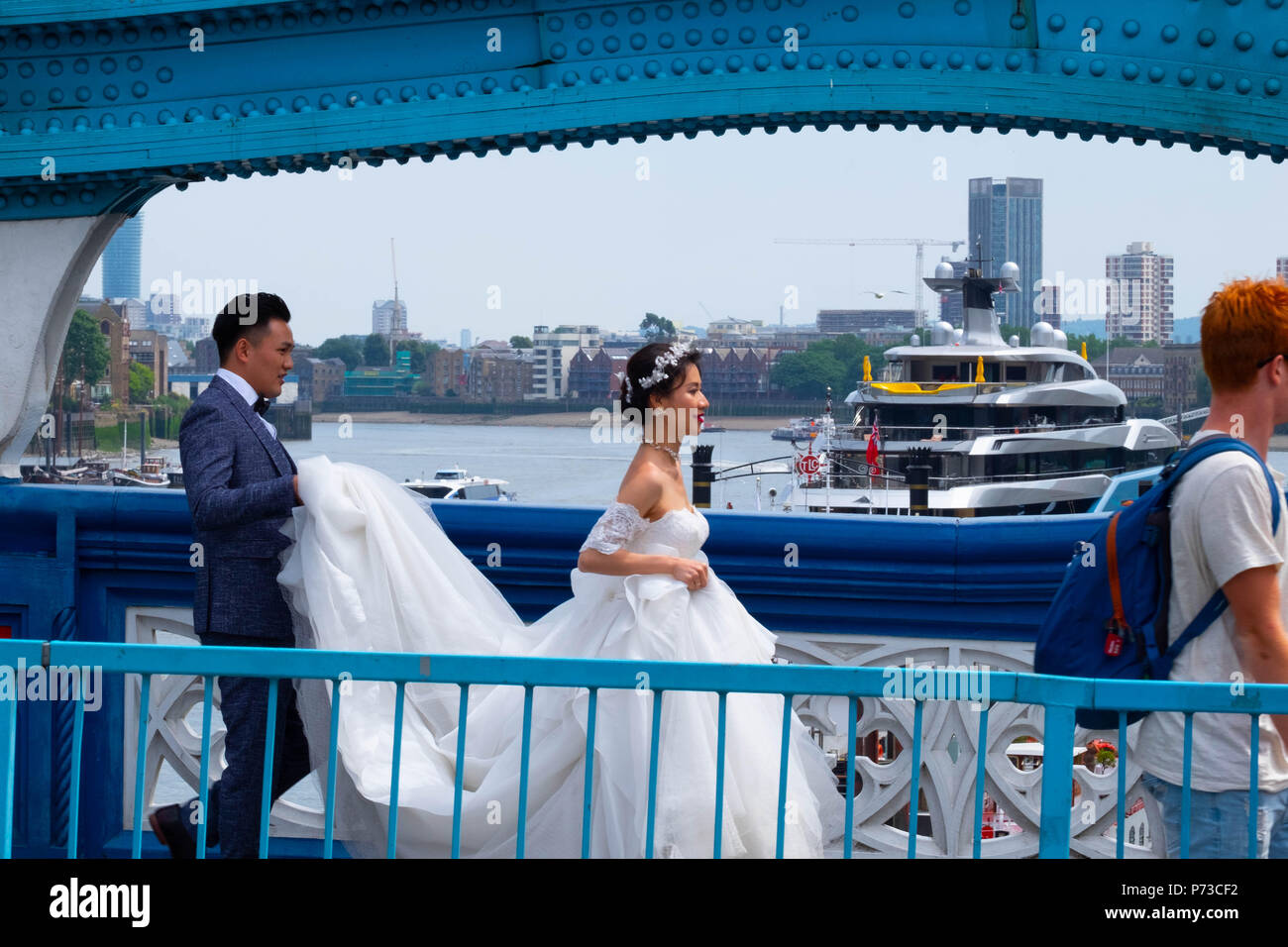 London, England. 4th July 2018. A couple have their wedding photos taken on London's Tower Bridge among all the tourists on another very hot day. The present heatwave is set to continue. ©Tim Ring/Alamy Live News Stock Photo