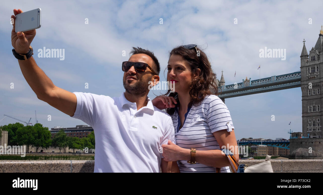 London, England. 4th July 2018. Georgia and her boyfriend, tourists from Greece, take a selfie near Tower Bridge on another very hot day. The present heatwave is set to continue. ©Tim Ring/Alamy Live News Stock Photo
