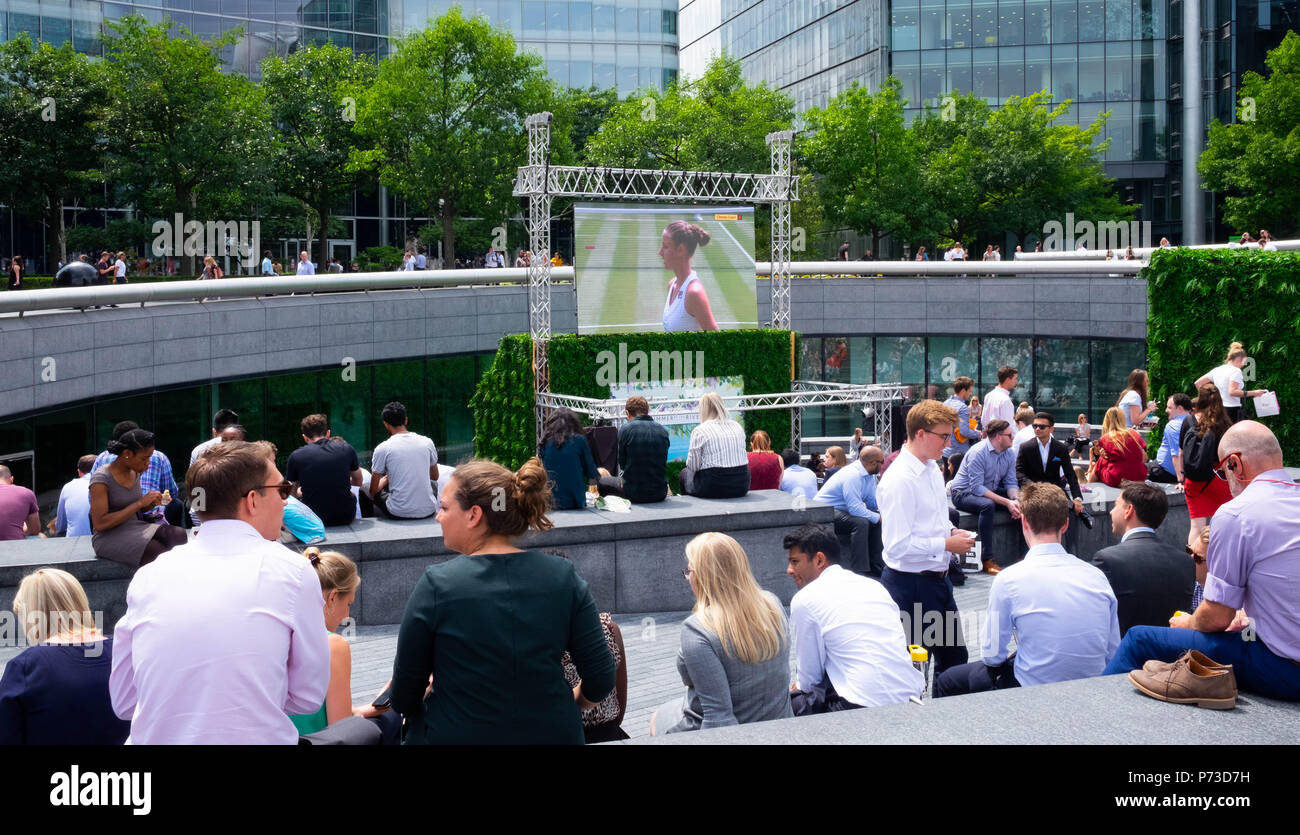 London, England. 4th July 2018. Tourists and office workers watch the tennis at Wimbledon on a giant screen on another very hot day. The present heatwave is set to continue. ©Tim Ring/Alamy Live News Stock Photo