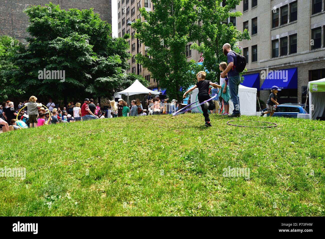 Chicago, Illinois, USA. Children play with Hula Hoops as others take in a concert in a small park as part of the annual Printers Row Lit Fest. - Stock Image