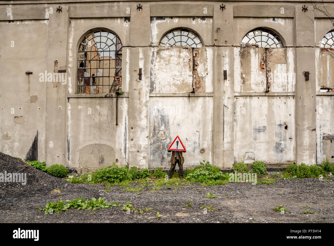 Unidentified man holds a red traffic triangle warning sign in front of his head near a ruined building. - Stock Image