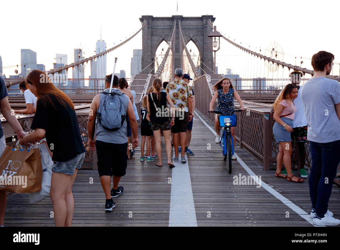 Pedestrians, and cyclists over on the Brooklyn Bridge foot path - Stock Image
