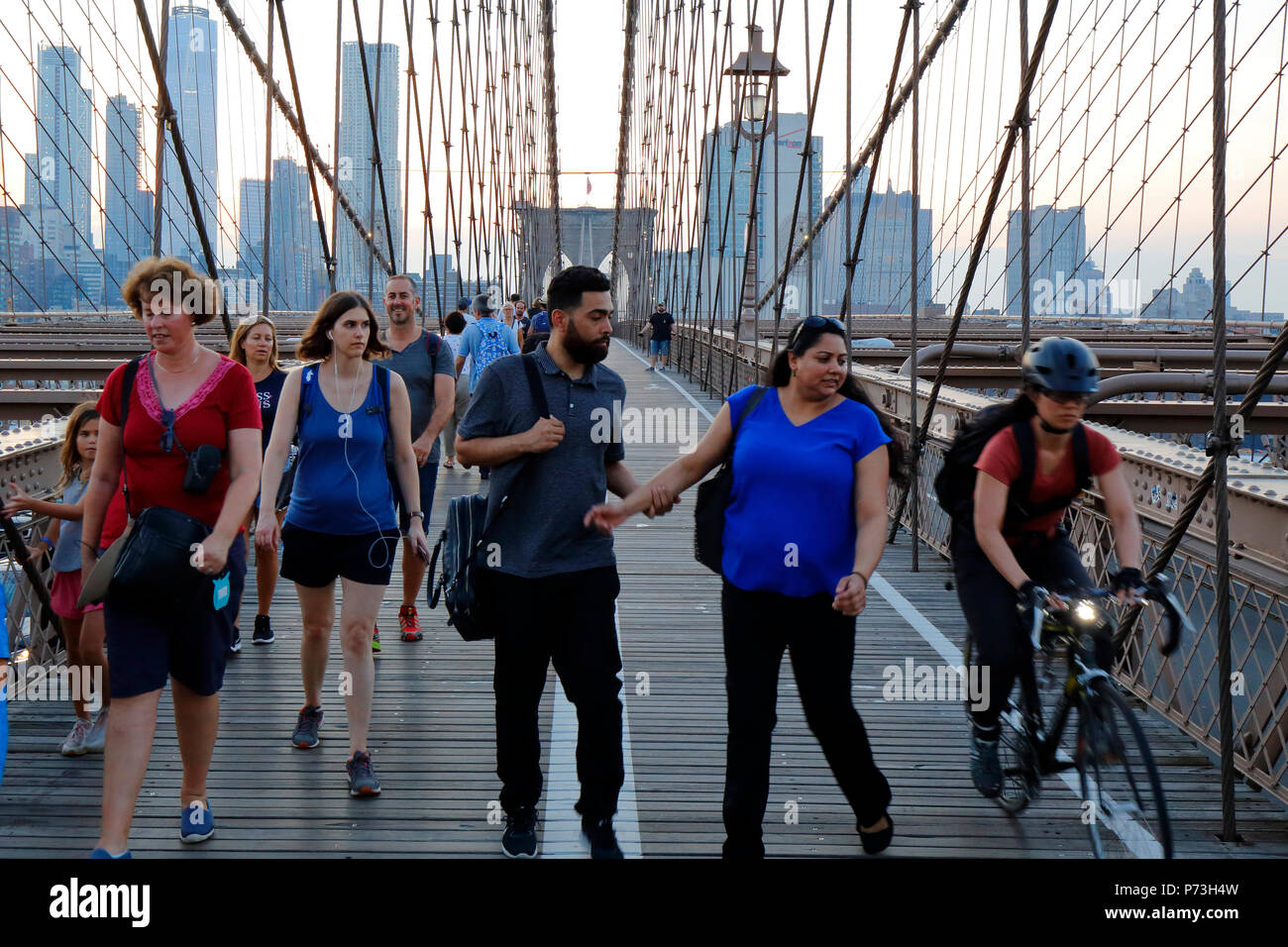 Pedestrians, and cyclists avoid conflict on the Brooklyn Bridge foot path. - Stock Image