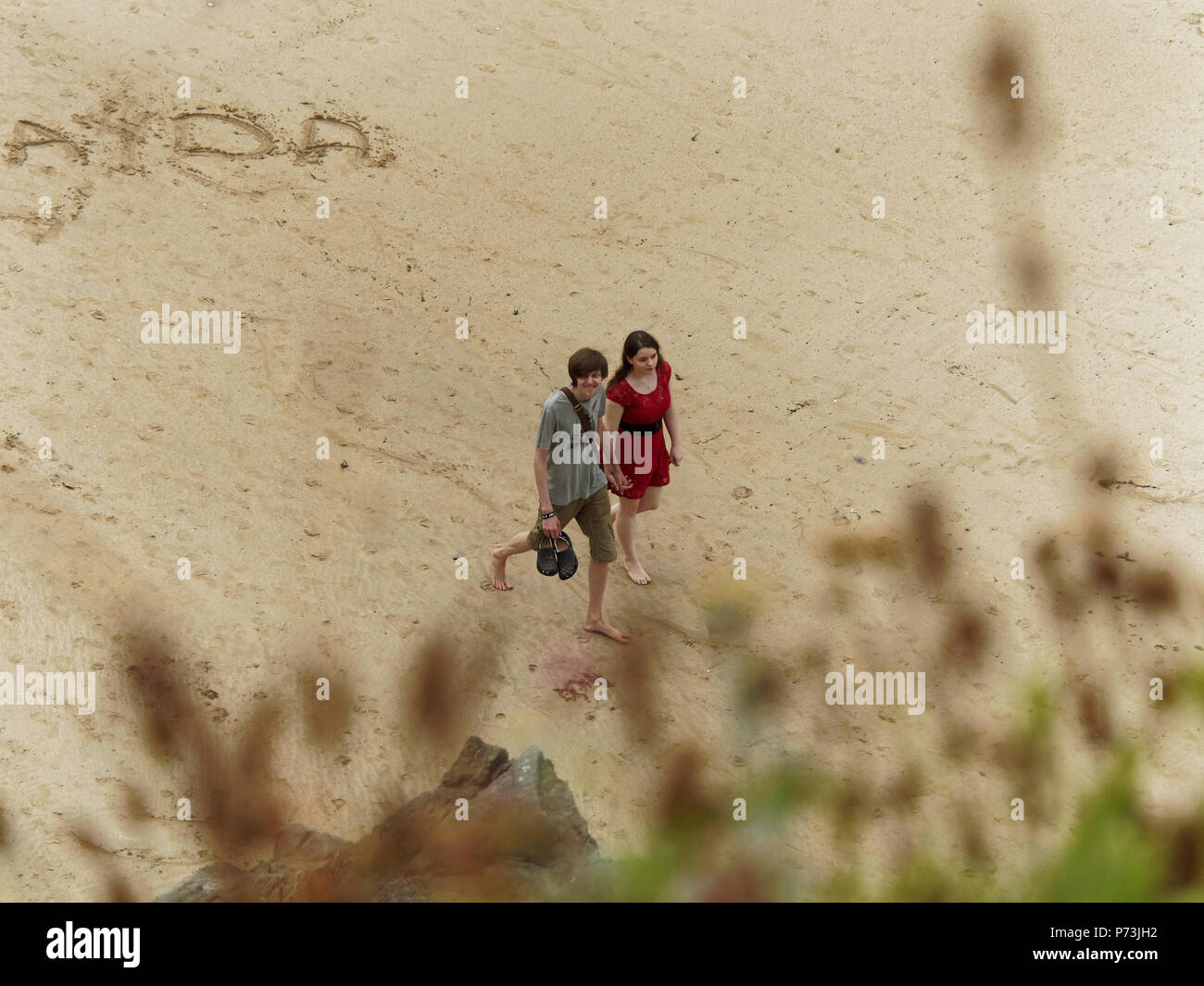 romantic couple on beach distance view.30th, June, 2018  Robert Taylor/Alamy Live News.  Newquay, Cornwall, UK. - Stock Image