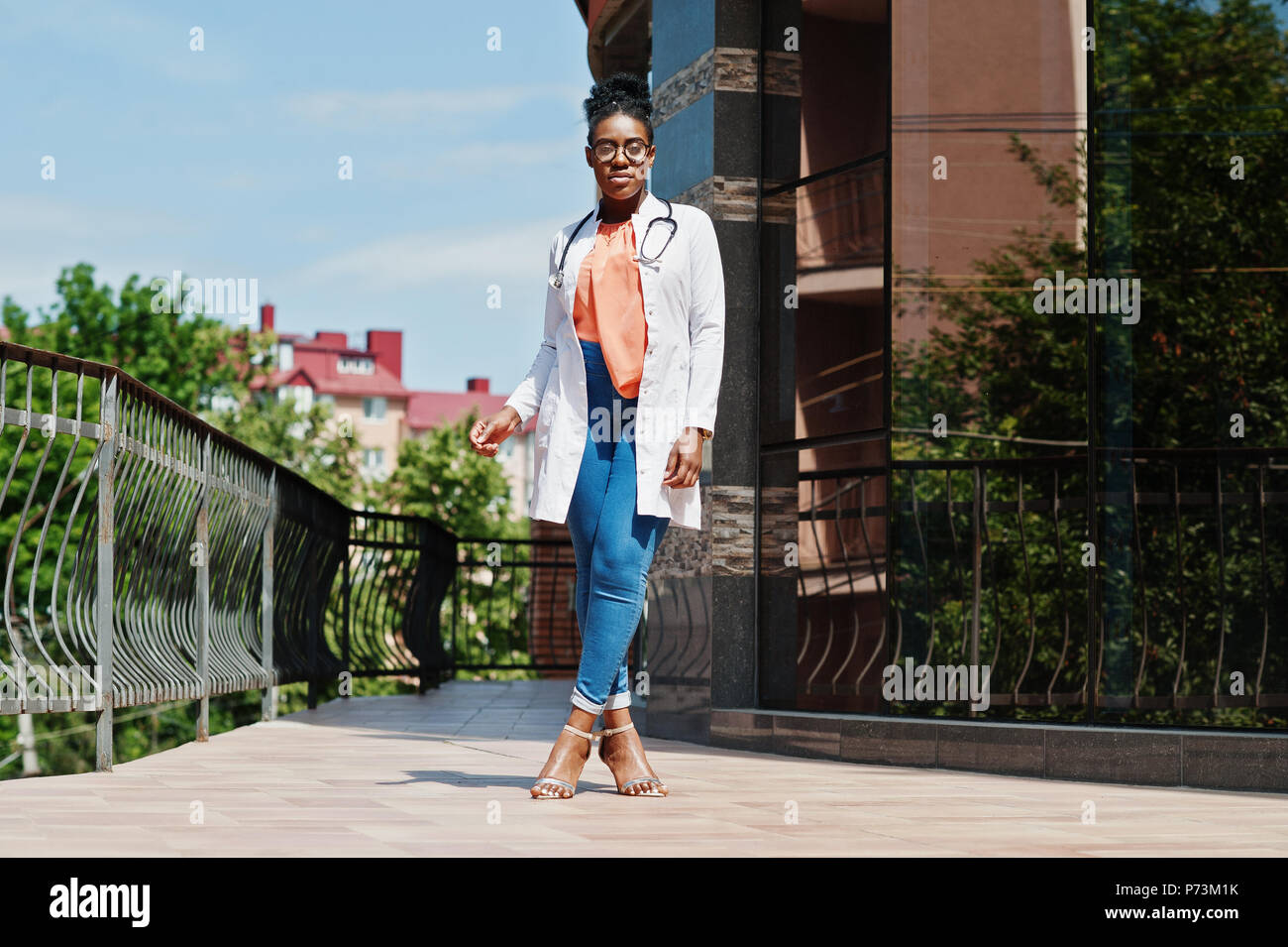 African american doctor female at lab coat, glasses with stethoscope posed outdoor against clinic. - Stock Image