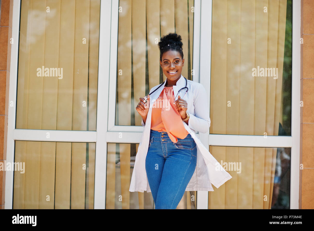 African american doctor female at lab coat with stethoscope posed outdoor against clinic. Stock Photo