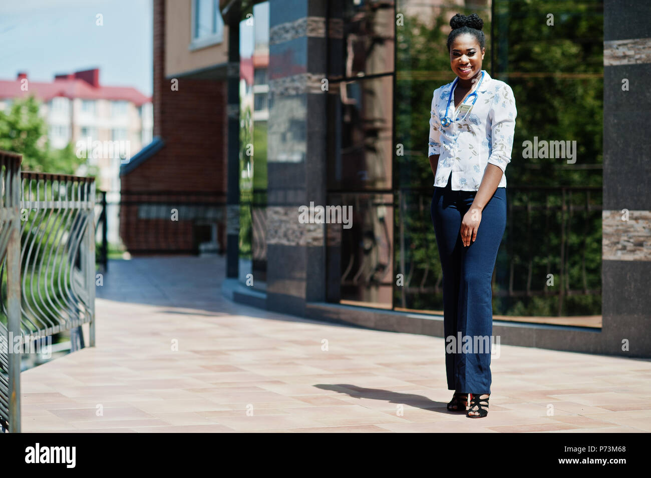 African american doctor female with stethoscope posed outdoor against clinic. - Stock Image