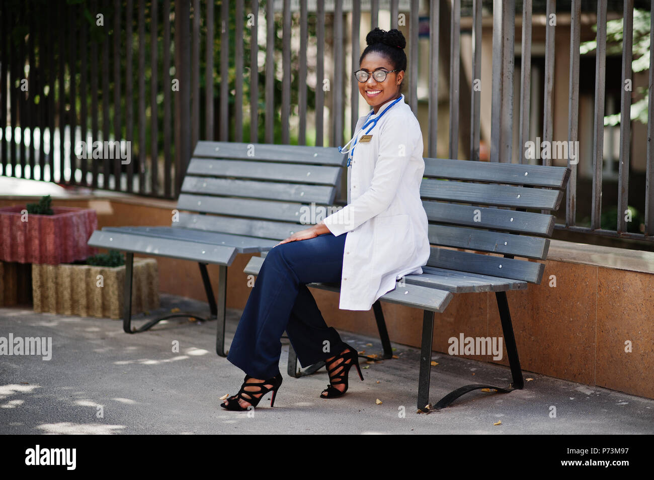 African american doctor female at lab coat with stethoscope posed outdoor sitting on bench. - Stock Image