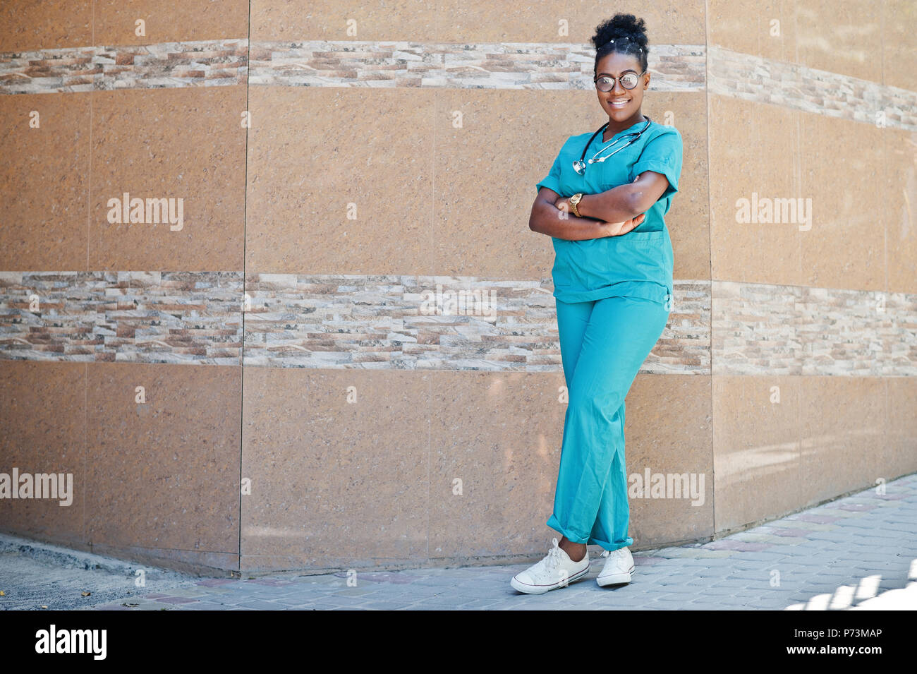 African american doctor female at lab coat with stethoscope posed outdoor against clinic. - Stock Image