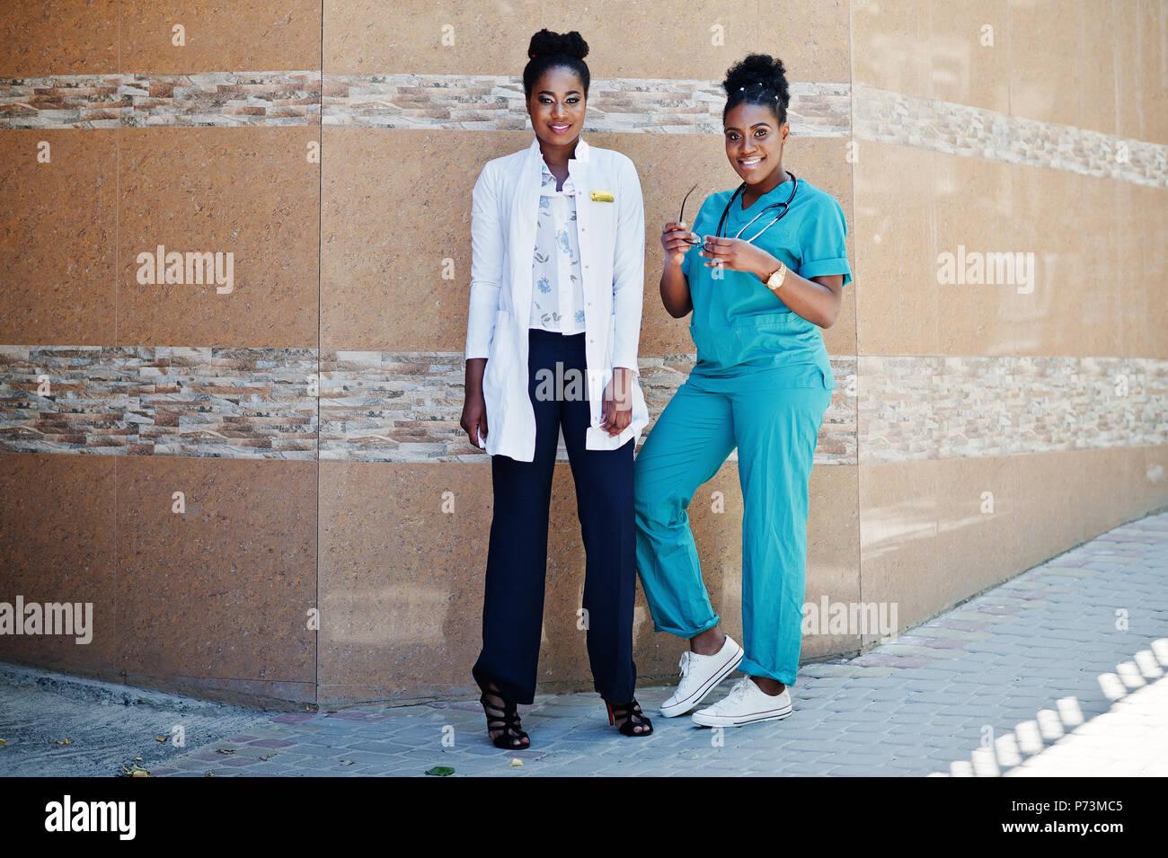 Two african american doctors female at lab coat with stethoscope posed outdoor against clinic. - Stock Image