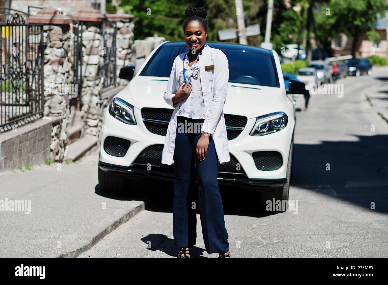 African american doctor female at lab coat with stethoscope posed outdoor against white suv car. - Stock Image