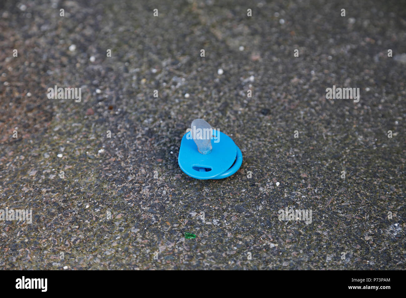 Discarded babies dummy on path - Stock Image