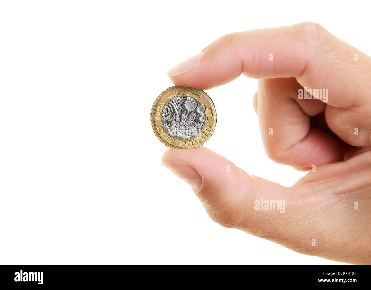 New Pound Coin Held Between the Fingers of a Womans Hand, Cut Out - Stock Image