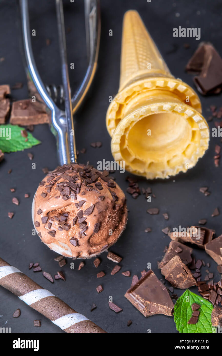 Chocolate ice cream in scoop with wafer sticks, cone and chocolate on a black slate board. Focus on ice cream in scoop. - Stock Image