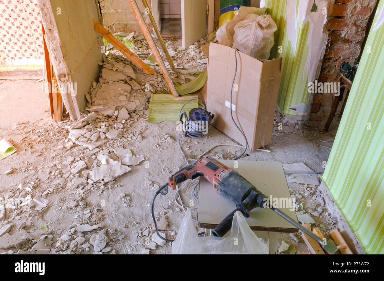 Drill on the dirty and dusty floor in a house under construction. - Stock Image