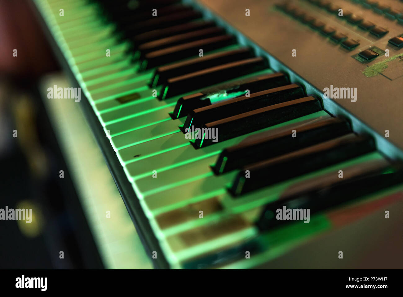 Keyboard of synthesizer in detail in tinted green - Stock Image