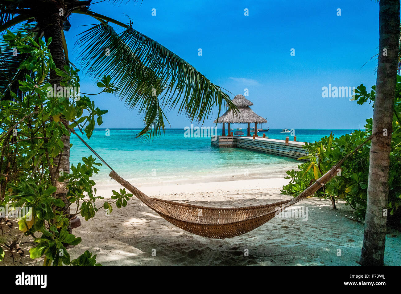 Take a pause. Maldives beautiful beach background white sandy tropical paradise island with blue sky sea water ocean Stock Photo