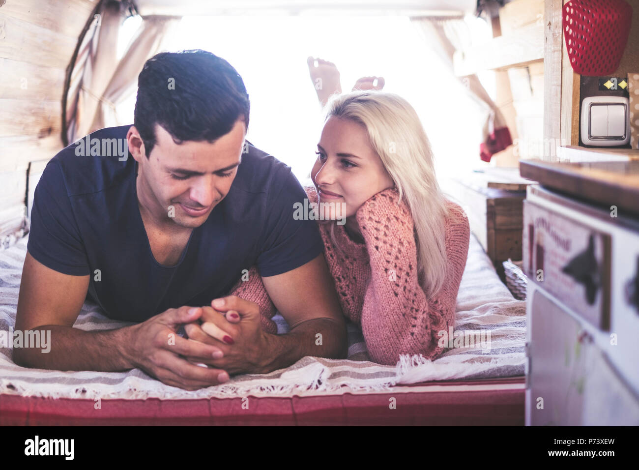 caucasian couple in love and romantic scene inside an old vintage camper ready to travel and have a vacation together with happiness and joy. blonde b - Stock Image