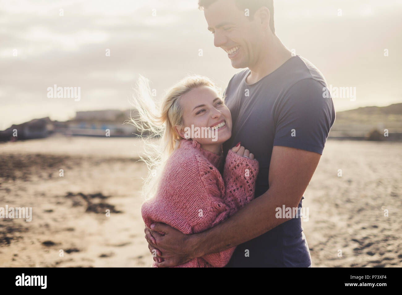 aucasian couple in love and romantic scene inside an old vintage camper ready to travel and have a vacation together with happiness and joy. blonde be - Stock Image
