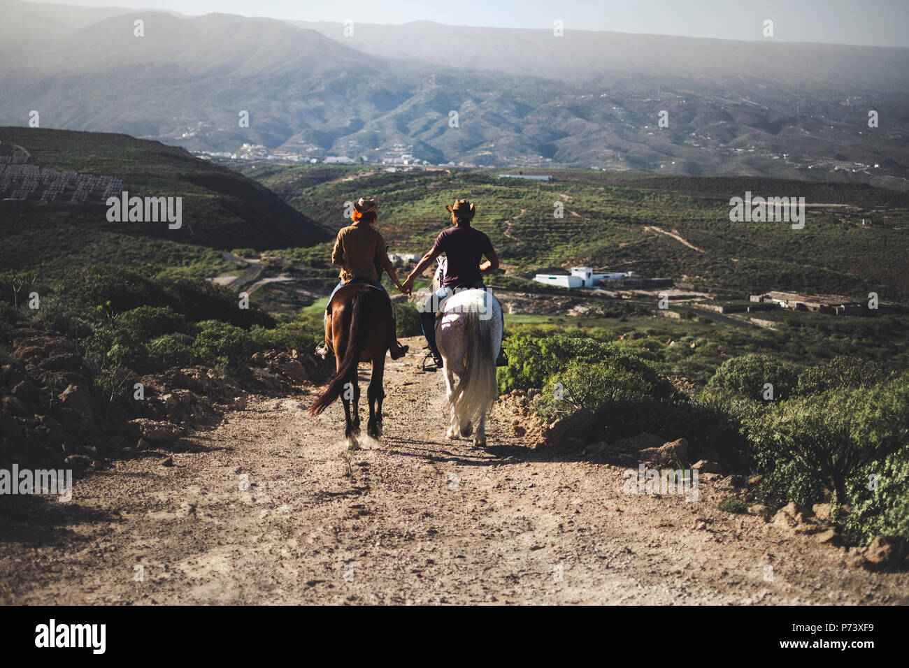 couple in love riding two beautiful horses stay together in a travel adventure for alternative lifestyle and vacation. togetherness couple traveling c - Stock Image