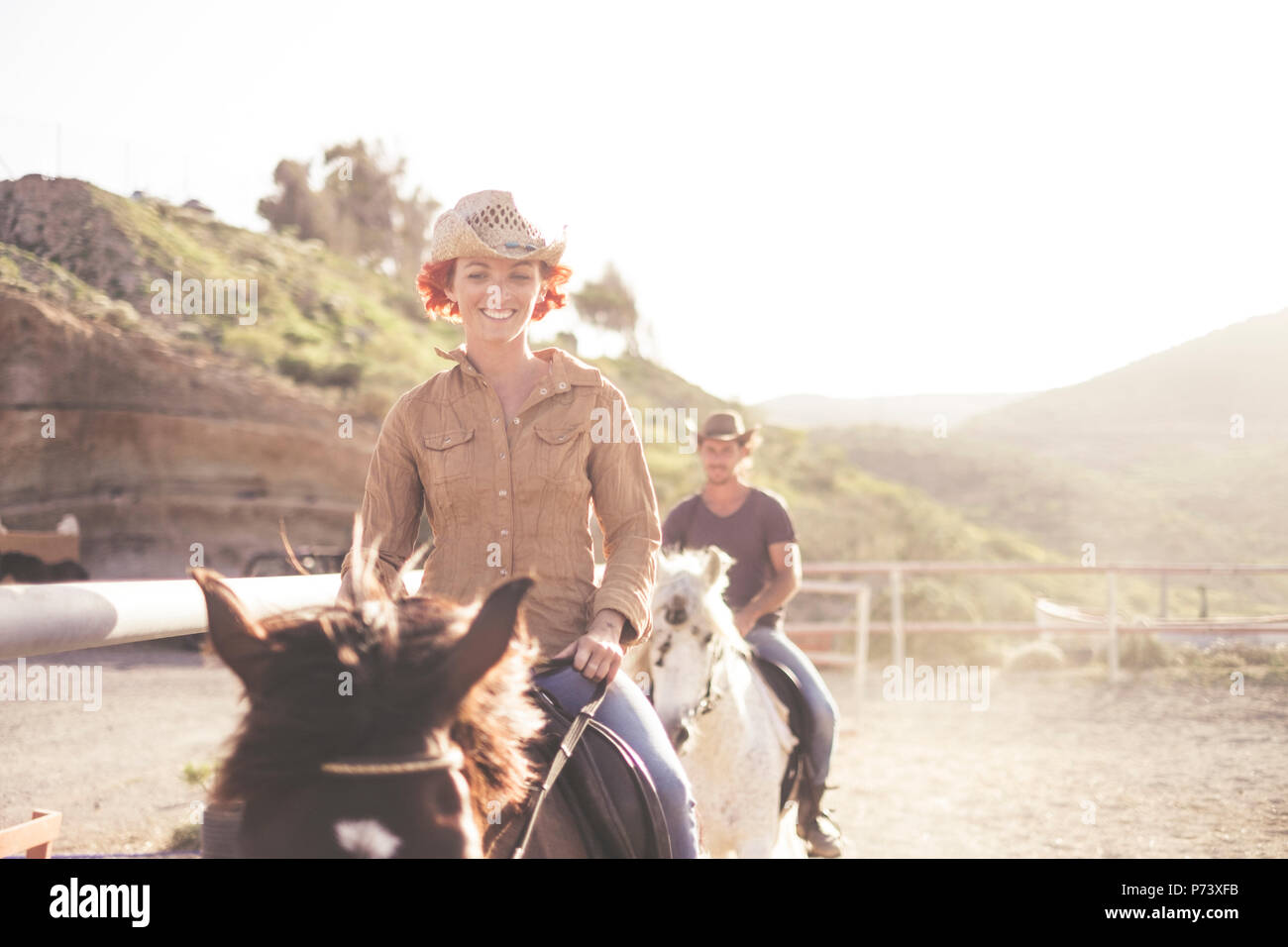 nice caucasian couple friends young people ride beautiful horses outdoor in a school. sun backlight for bright image in warm filter. friendly scene wi - Stock Image