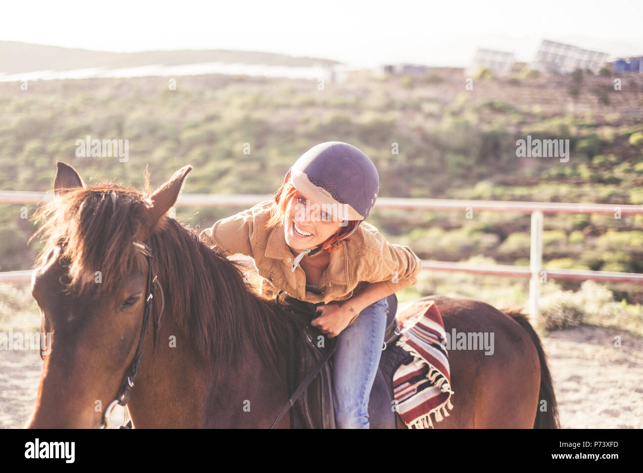 ride with a helmet for a beautiful attractive young woman with nice smile. jeans and casual clothes for outdoor girls in leisure activity with brown h - Stock Image