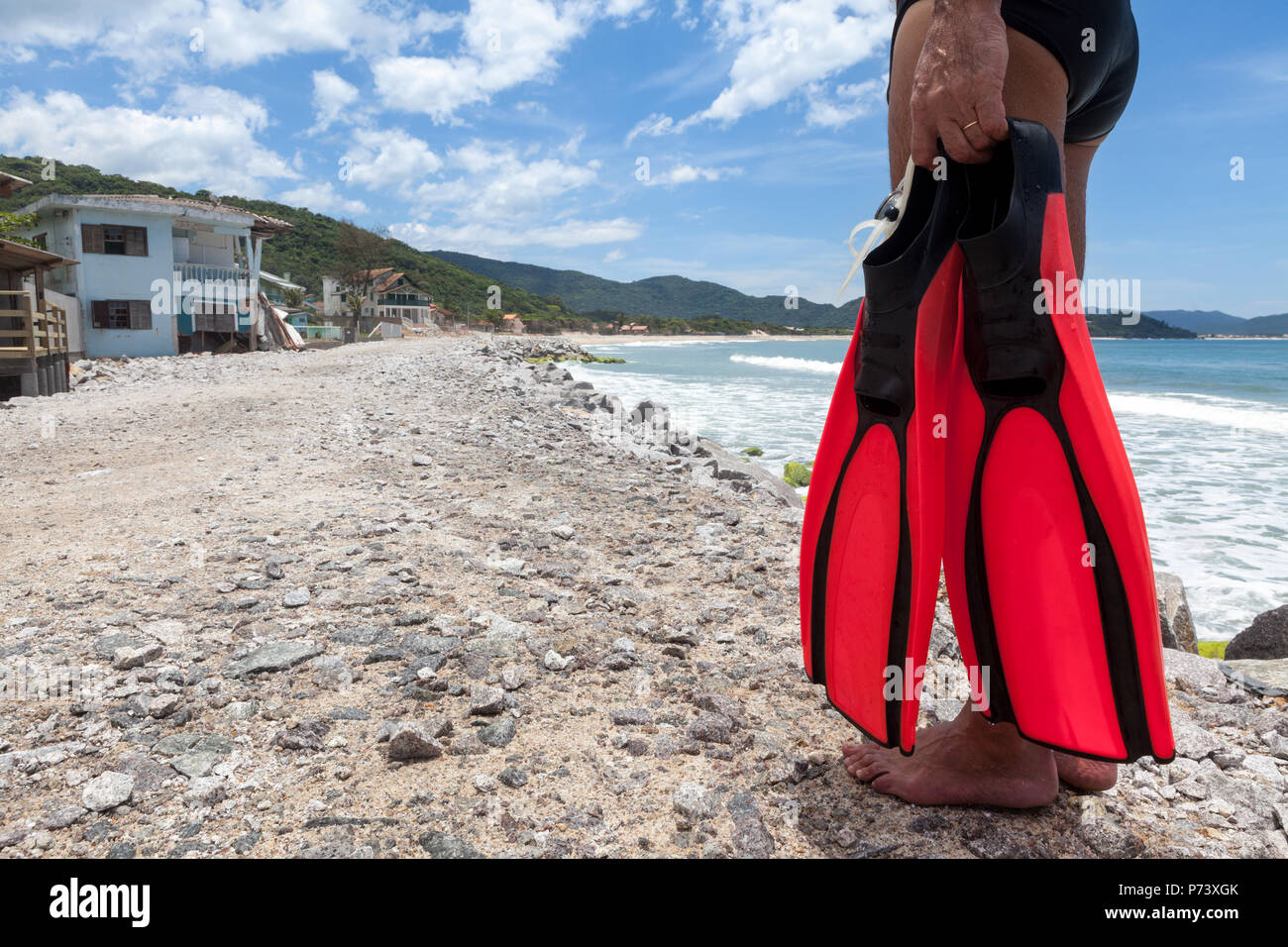 Florianopolis, Santa Catarina, Brazil. Man holding diving fins on street destroyed by the sea next to beach. Effect of rising sea levels. - Stock Image