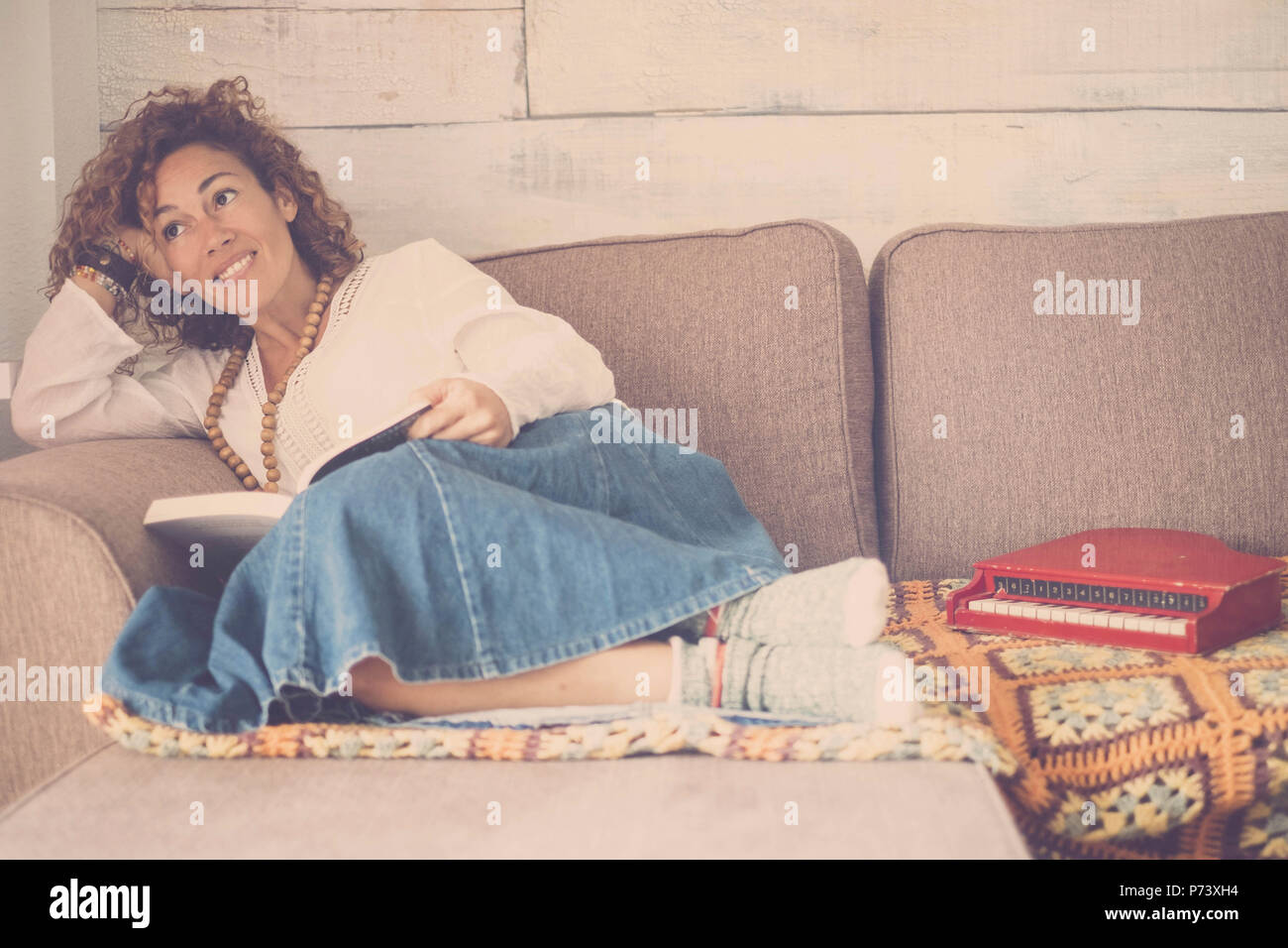 beautiful caucasian woman lay down relaxing on the sofa at home loooking outside the window. little piano toy at her feet. creativity feeling for nice - Stock Image