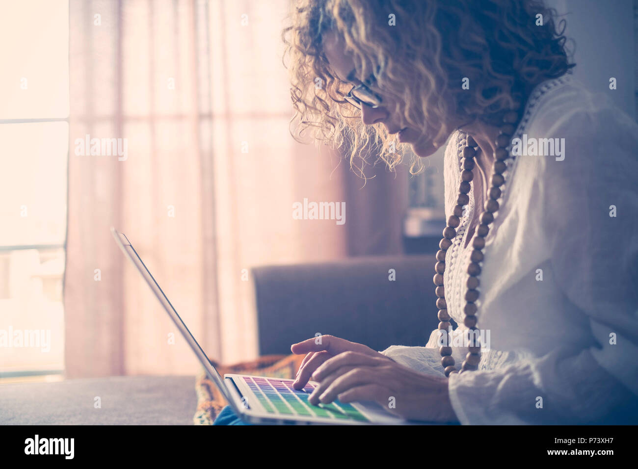 beautiful concentrated middle age caucasian woman working on the laptop with colored keywords. writer work at home for alternative lifestyle and offic - Stock Image