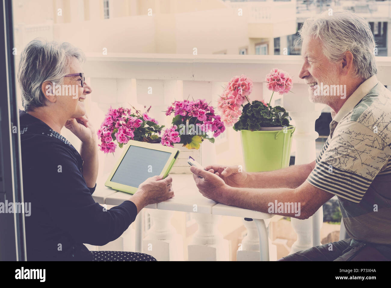 senior happy caucasian couple in outdoor leisure activity using technology ti chat work and do videoconference with friends. lifestyle at home in mode - Stock Image