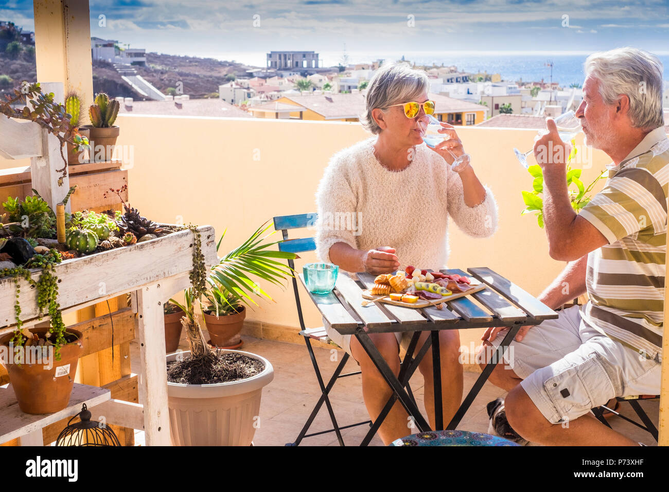 caucasian senior adult couple eat and enjoy leisure outdoor together eating and drinking a breakfast in a sunny morning on the rooftop with ocean view - Stock Image