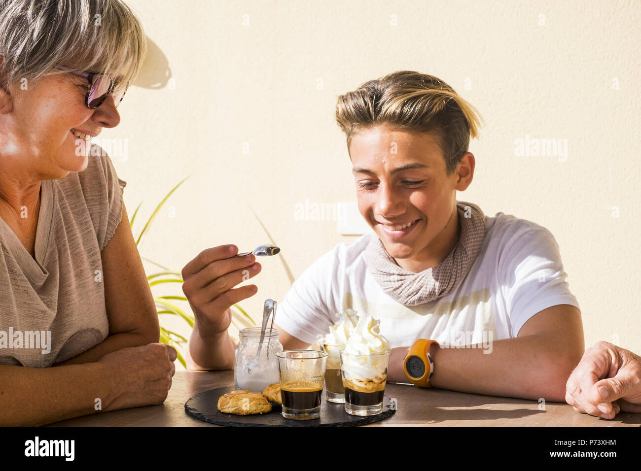 mixed generations caucasian people eating together a breakfast in an outdoor vacation morning. old and young male and woman family grandmother and nep - Stock Image